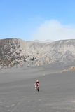 A MAN WEARING HAT AND GUIDE A BIKE IN THE SEA OF SAND Stock Photo