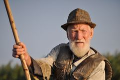 Man Wearing Hat Holding Wooden Rod Under Gray Sky Royalty Free Stock Image