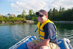 Man smiles on the ocean. A man wearing a hat and a lifejacket grins with glee as he drives a small blue dinghy around a lake or sea stock image
