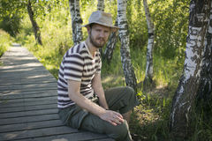 Man wearing a hat. Sitting on the bridge in the wood Royalty Free Stock Photo