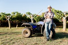 Man standing next to truck in vineyard Royalty Free Stock Image