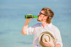 Man wearing hat and sunglasses enjoing beer in a. Man wearing hat and sunglasses enjoying beer in a bottle on the beach on beautiful summer holidays day Royalty Free Stock Photo