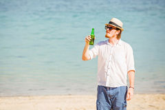 Man wearing hat and sunglasses enjoing beer in a Stock Photo