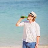 Man wearing hat and sunglasses enjoing beer in a. Man wearing hat and sunglasses enjoying beer in a bottle on the beach on beautiful summer holidays day Stock Photos