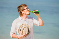Man wearing hat and sunglasses enjoing beer in a. Man wearing hat and sunglasses enjoying beer in a bottle on the beach on beautiful summer holidays day Royalty Free Stock Images