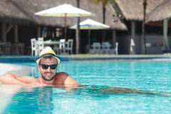 Man wearing hat and sunglasses relaxing at the pool Royalty Free Stock Photo
