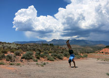 Man wearing a hat, t-shirt, shorts, and slippers does Handstands Stock Images