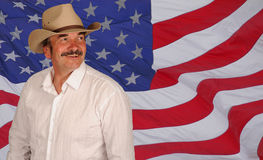 Man wearing hat on US flag. A studio portrait of a man wearing a white shirt and cowboy hat, against a US flag.  Model looks somewhat like Burt Reynolds Stock Photo