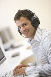 Man wearing headphones in computer room typing. And smiling Royalty Free Stock Image