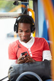 Man Wearing Headphones Listening To Music On Bus Journey. Holding Mobile Phone Device Royalty Free Stock Photo