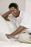 Man Wearing Headphones Listening To Music On Laptop Royalty Free Stock Photos