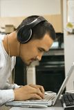 Man wearing headphones using laptop. Close-up side view of Asian young adult man leaning over laptop typing on keyboard wearing headphones Royalty Free Stock Photography