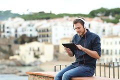 Man wearing headphones watching content on a tablet. Serious man wearing headphones watching media content on a tablet sitting on a ledge stock image