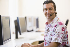 Man wearing headset in computer room smiling. At camera Stock Images