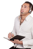 Man wearing a headset taking notes. Man wearing a headset staring upwards as he listens to the conversation while taking notes, conceptual of a call centre, help Stock Images