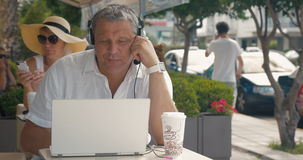 Man wearing headset video chatting in outdoor cafe. Senior man wearing headset and having a video chat on laptop while sitting in street outdoor cafe. Woman stock video