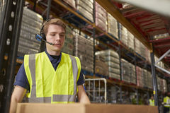 Man wearing a headset working in a distribution warehouse Stock Photo