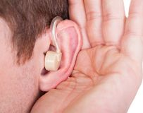 Man Wearing Hearing Aid And Listening For A Quiet Sound Stock Image
