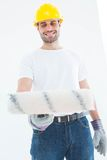 Man wearing helmet while using paint roller Royalty Free Stock Image