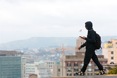 Free Man Wearing Hoodie Crosses Street In Contemporary San Francisco Scene Stock Photos - 59196593