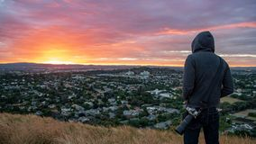Man wearing hoody watching sunrise over Auckland city stock images