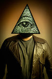 Man Wearing Illuminati Eye of Providence Mask. A male figure in a leather trench coat wearing an Illuminati symbol eye of providence, or all seeing eye mask Stock Photo