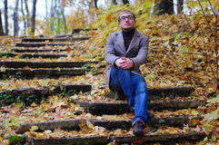 A man wearing a jacket with glasses in autumn. On the stairs Stock Images