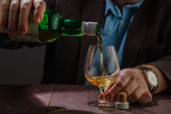 Man wearing jacket holding a glass of whiskey at the bar counter Stock Image