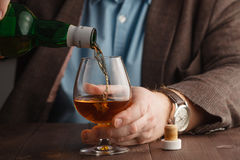 Man wearing jacket holding a glass of whiskey at the bar counter Stock Images