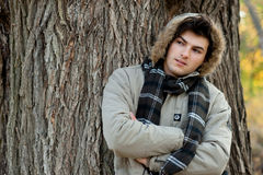 Man wearing a jacket with a hood in autumn park. Royalty Free Stock Image