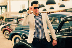 Man wearing jacket and shirt with old cars. Portrait of a young handsome man, model of fashion, wearing jacket and shirt with old cars stock images