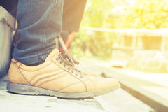 Man wearing jeans and brown shoes. Sitting on stairs with sun light Royalty Free Stock Images