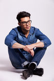Man wearing jeans shirt and glasses, sitting Stock Images