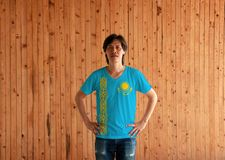 Man wearing Kazakhstan flag color shirt and standing with akimbo on the wooden wall background. A gold sun above eagle on blue field and national ornamental stock photo