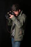 Man wearing khaki jacket takes photo. Close up. Black background Stock Photos