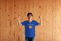 Man wearing Kosovo flag color of shirt and standing with raised both fist on the wooden wall background. A blue field charged with a map of Kosovo in gold stock photo