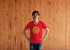 Man wearing Kyrgyzstan flag color shirt and standing with akimbo on the wooden wall background. Red field with a yellow sun with forty uniformly spaced rays royalty free stock photos