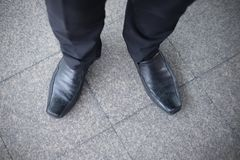 Man wearing leather black shoes standing on tile floor. Close up legs of a man wearing leather black shoes standing on tile floor. View from above Royalty Free Stock Photo