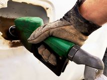 Man wearing leather gloves pumping diesel. Closeup of gloved hand pumping diesel into a white truck Royalty Free Stock Photos