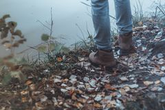 A man wearing light jeans and boots stands by the river. Kind of legs. Autumn. Evening. Close-up stock photo