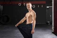 Man Wearing Loose Jean In The Gym. Young Athlete Man Wearing Loose Jean Showing His Weight Loss In The Gym Stock Photography