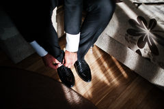 Man wearing luxury patent leather shoes on sunlight with shadows. Gathering of groom on wedding day Royalty Free Stock Images