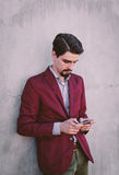 Man Wearing Maroon Blazer Leaning on Gray Concrete Wall While Using His Smartphone Stock Photography