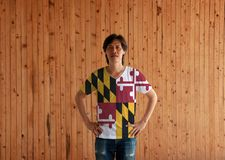Man wearing Maryland flag color shirt and standing with akimbo on the wooden wall background. The states of America stock image