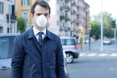 Man walking in the city wearing protection mask against smog air Royalty Free Stock Images