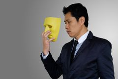 Man wearing mask. Asia businessman is wearing yellow mask on gray background with clipping path Royalty Free Stock Image