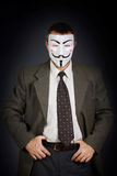 Man wearing mask of Guy Fawkes stands against dark background Royalty Free Stock Photography