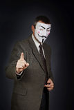 Man wearing  mask of Guy Fawkes wags his finger and stands against dark background Royalty Free Stock Photography