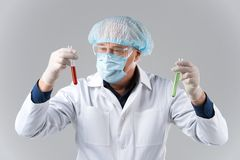 Man wearing mask looks at test tubes. Stock Image