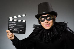 The man wearing mask with movie board. Man wearing mask with movie board Stock Photography